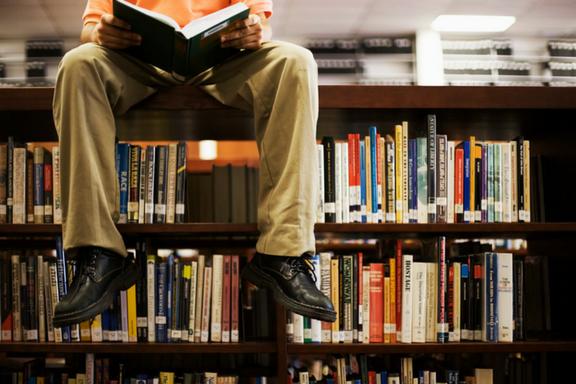 Boy sitting on library bookshelf holding book.