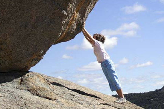 Boy holding up large rock.