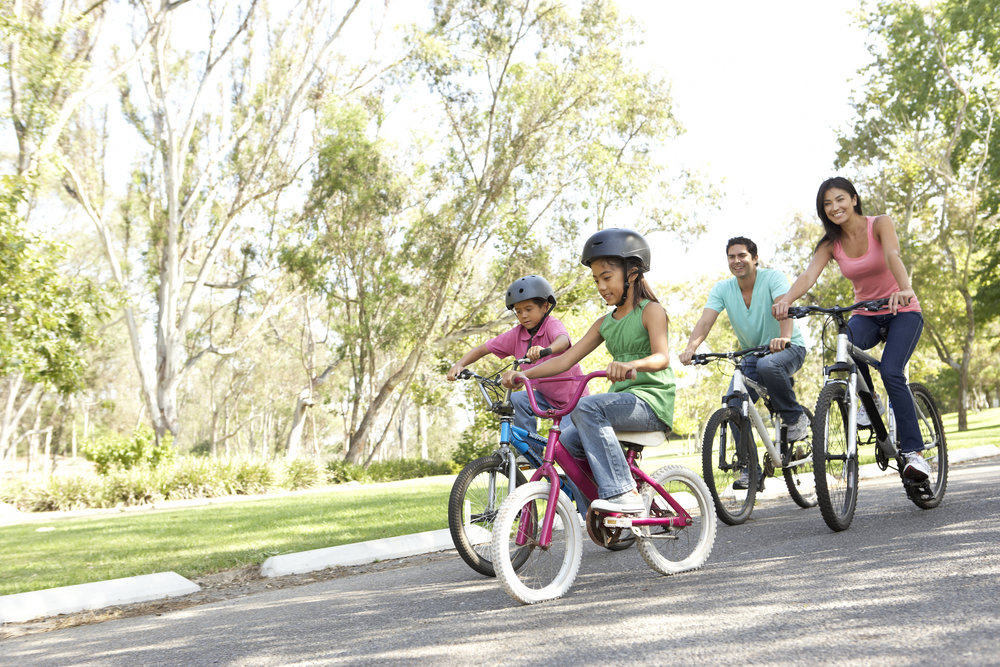 Hispanic Family rides bikes together.jpg