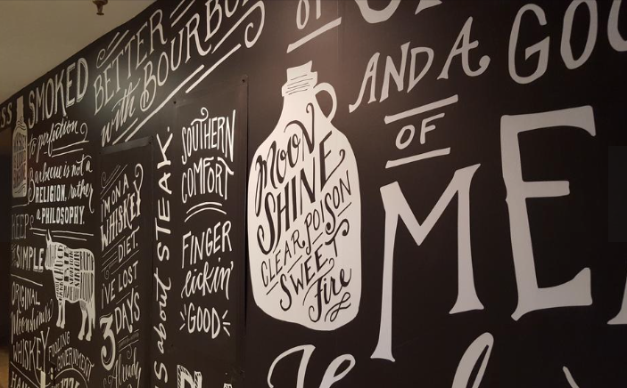 A hallway between the dining room and back lounge is influenced by the chalkboards outside of Southern barbecue joints advertising the day's offerings. © Photo by Washington Business Journal