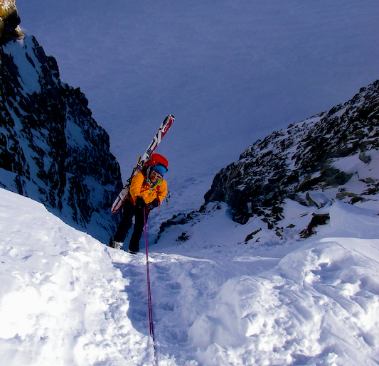 Rappelling with skis onto a couloir