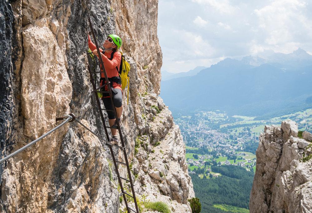 Climbing ladders on a via ferrata near Cortina