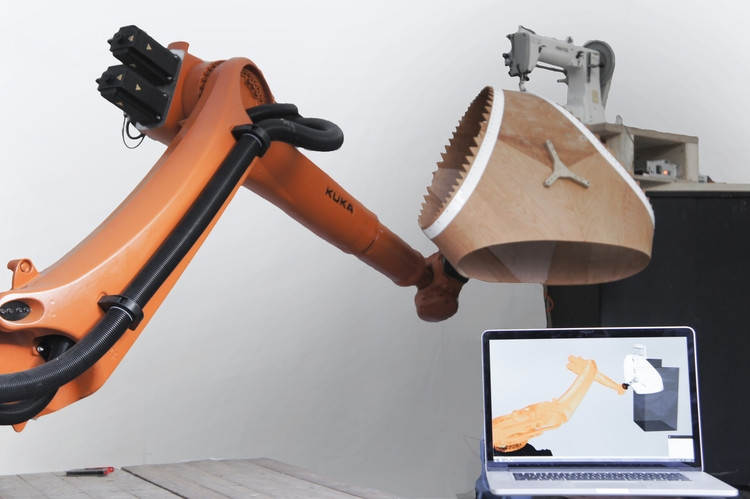 Process shot of a KUKA Robot arm prepping a component of the ICD Pavilion for assembly.