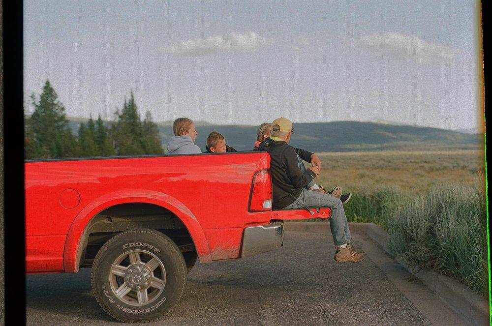 坐在紅色卡車上,等待日落的一家四口