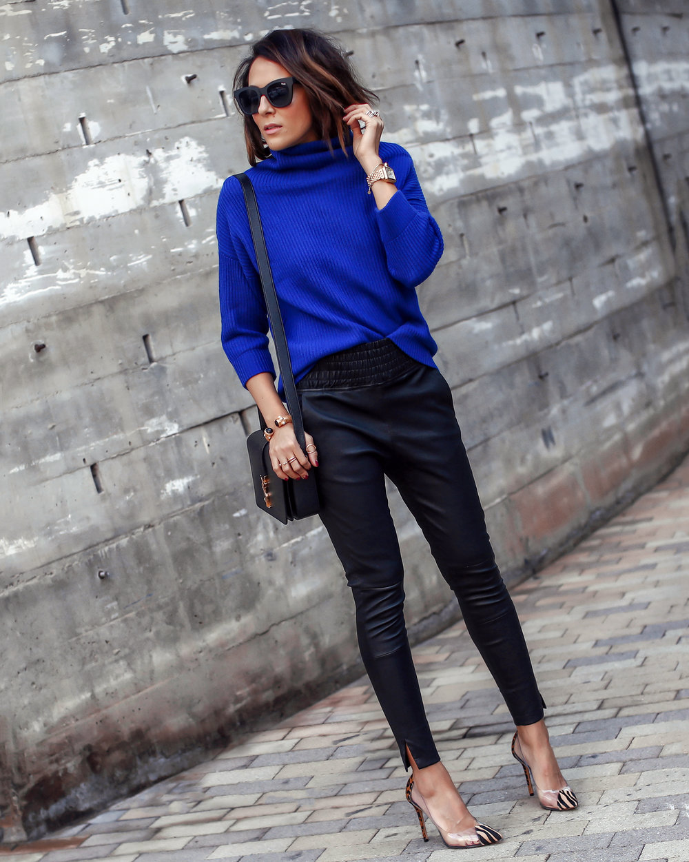 Brunette Woman Wearing Cashmere Sweater Leather Pants and PVC Leopard Pumps