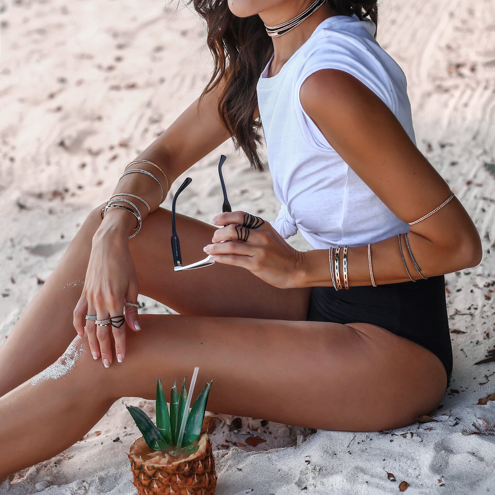Brunette Woman at Beach in Tee and Bikini Bottoms and Arme Del Amour Jewelry