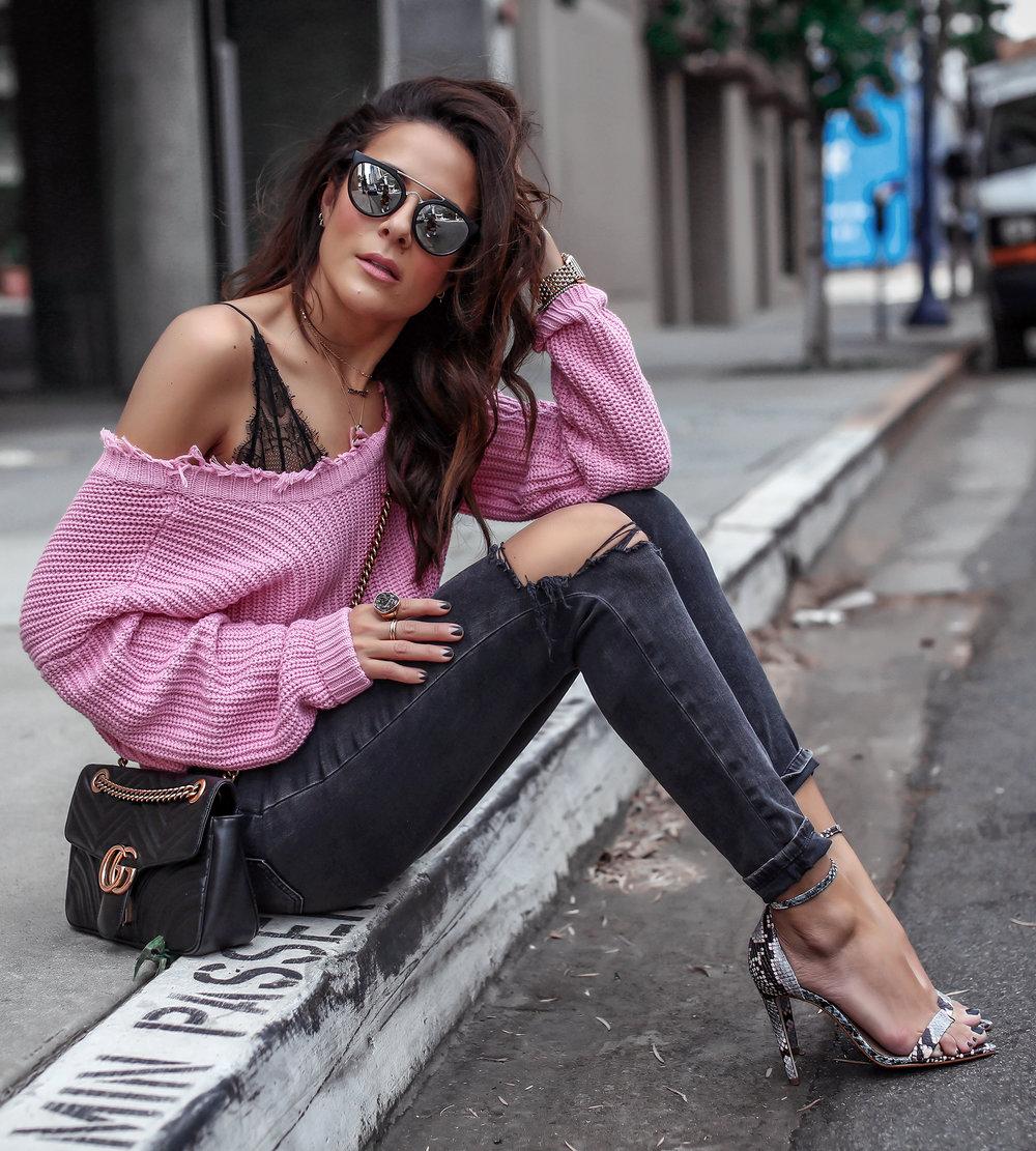 brunette woman sitting in pastel pink sweater