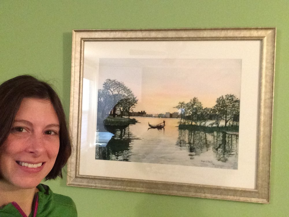 Laura with framed painting on her wall