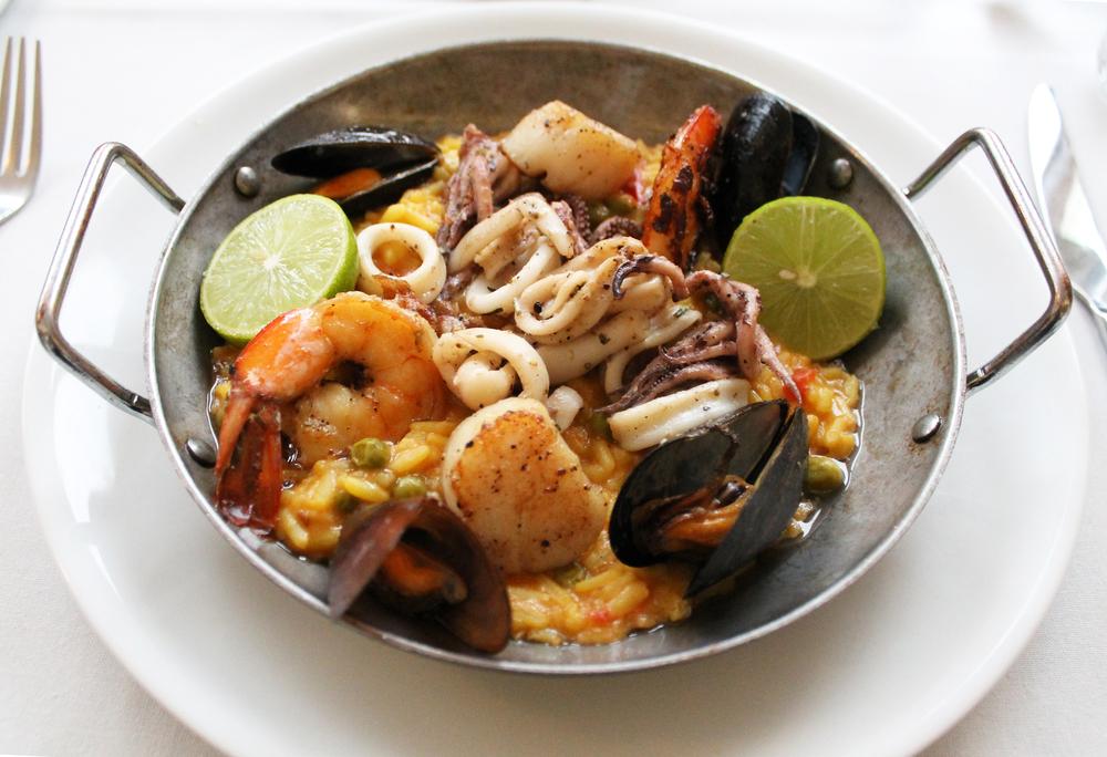 Paella del Mar: Black tiger shrimp, calamari, mussel, sea scallops,saffron rice, green pea, red bell pepper artichoke, saffron aioli, pimenton & oregano – Hojiblanca Olive Oil