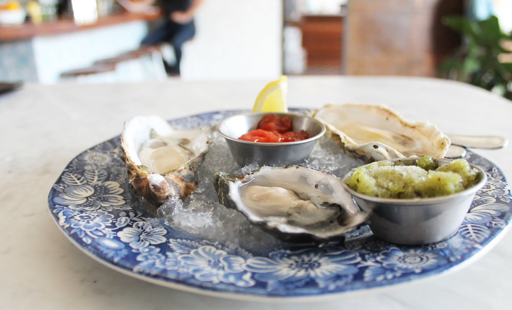 A selection of oysters with horseradish cocktail sauce and pickled shallot-cucumber sorbet.