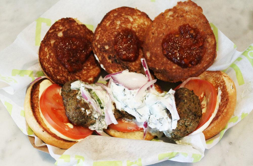 Yum Yum Lamb Sliders:Seasoned Ground Lamb, Homemade Tzatziki, Spicy Lime Sambal Sauce, Red Onion, Tomato, Garlic Aioli