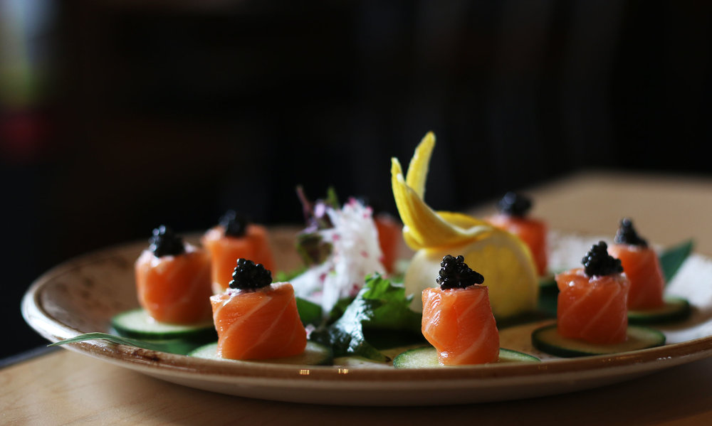 SALMON SASHIMI WITH CAVIAR: King salmon sashimi lightly rolled with Japanese onion chutney, topped with wild American paddlefish caviar on a cucumber crisp.