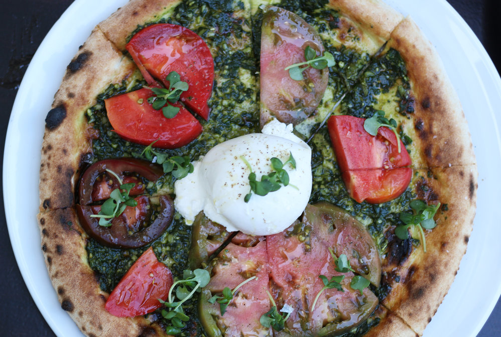 BURRATA SALAD PIZZA: Basil Pesto, Heirloom Tomatoes, Seasonal Greens, Balsamic Reduction