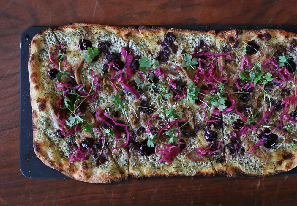 DUCK CONFIT: caramelized red onion, red wine pudding, toasted caraway, herbed goat cheese, pickled red cabbage, baby herbs