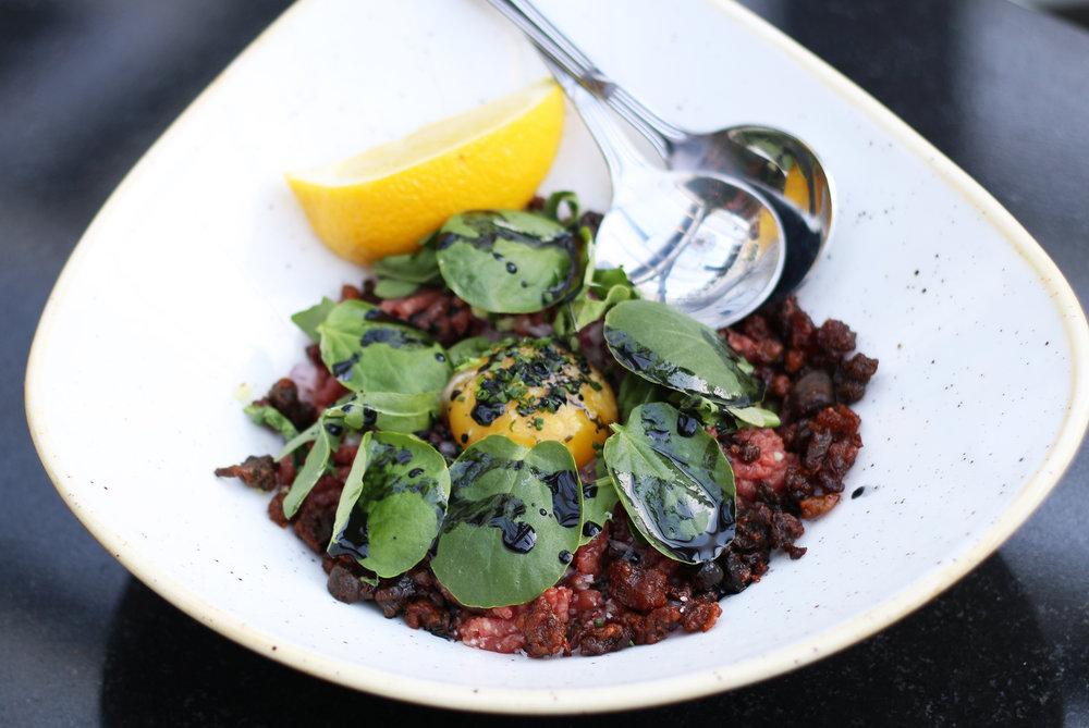 Beef Tartare: Ginger, chive, kalamata olive, arugula, egg yolk sauce