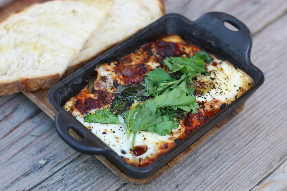 Shakshuka: farm eggs baked in a spicy tomato sauce, grilled bread for dippin'