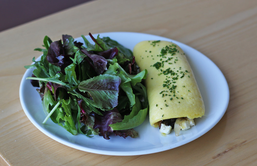 OMELETTE: caramelized onions, maitake mushrooms, feta cheese, mixed greens