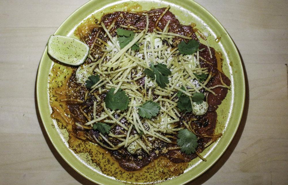 Beef Carpaccio Carne Asada: salsa macha, avocado crema, crispy potatoes