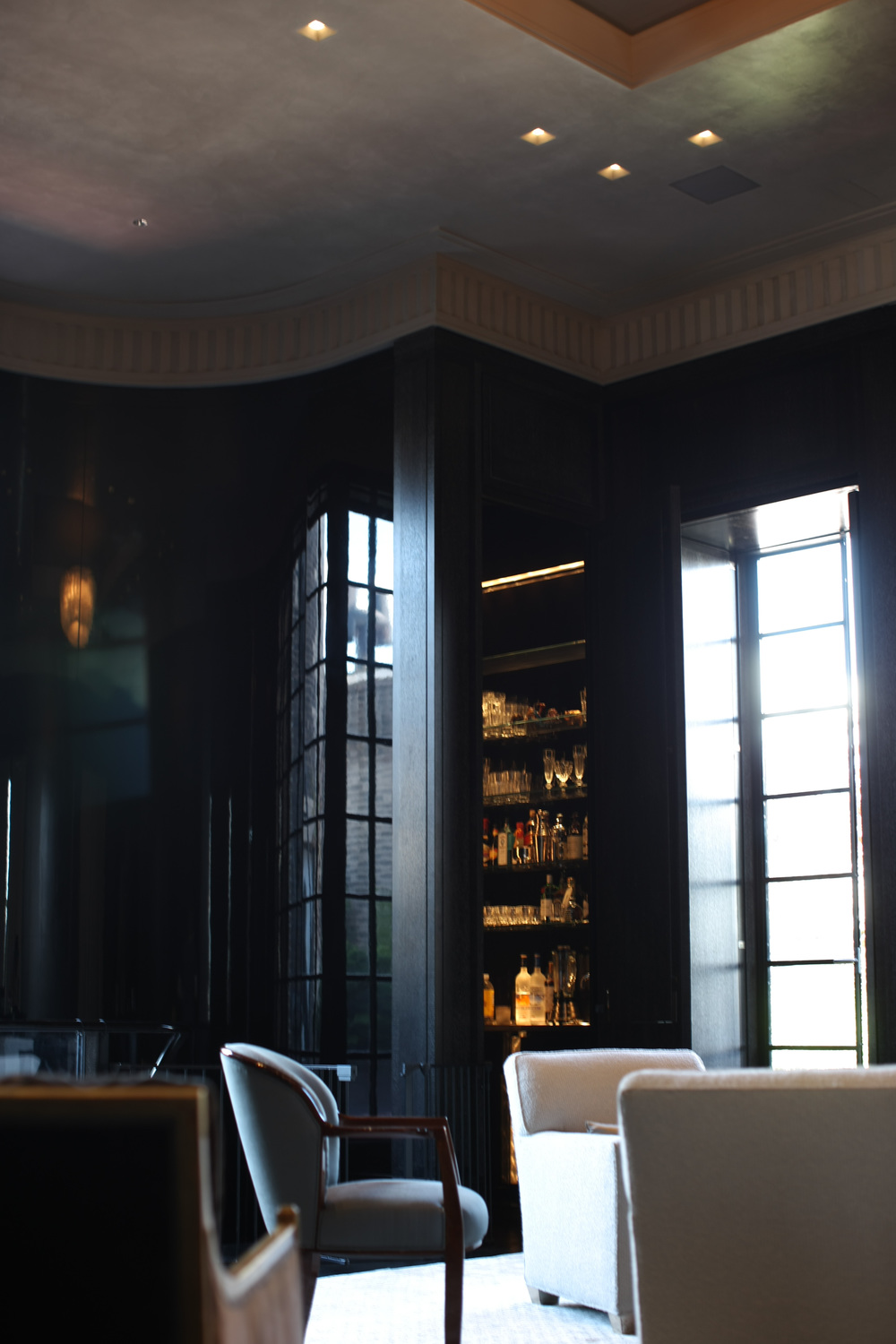 Wet bar - High gloss black lacquer wall panels and gilded ceiling