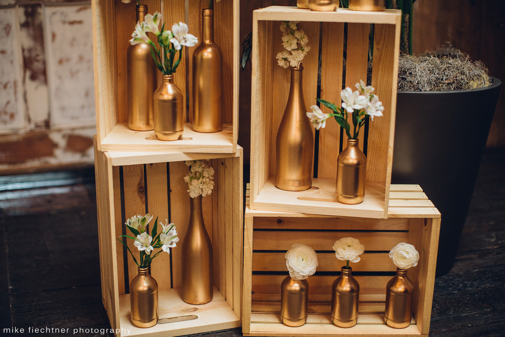 Alter display: Hand painted wine bottles nestled in raw wooden crates. Flowers by Stem Floral Design.