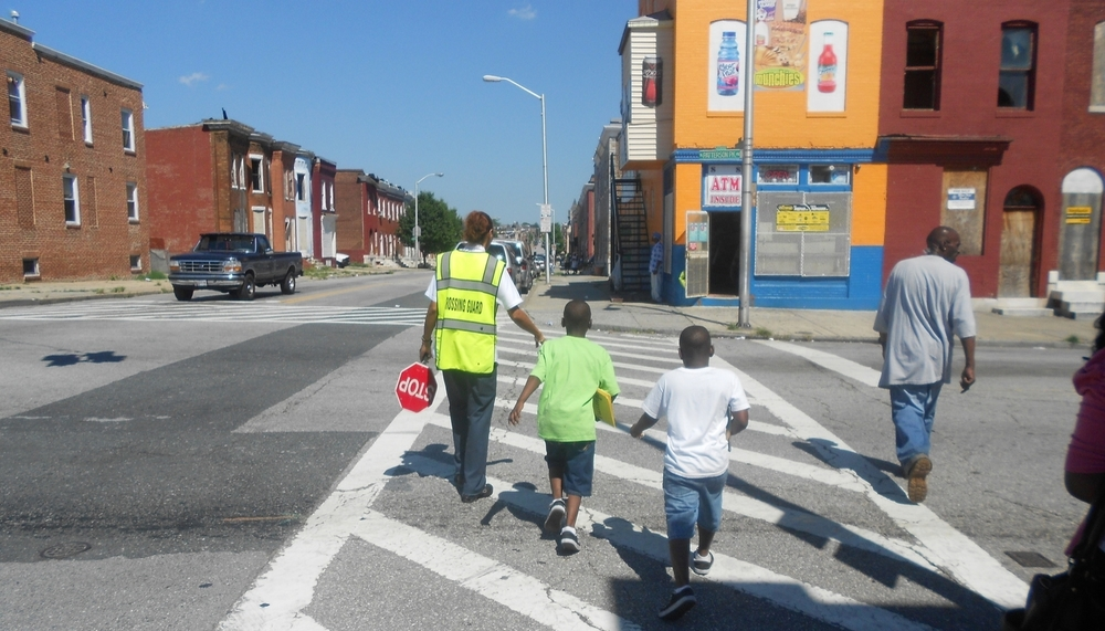 Kids crossing the street after school in East Baltimore. Photo Credit: Tykwan Bernie