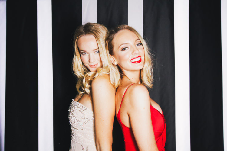 black-white-stripe-background-blondes-red-dress-red-lips-sisters-smiling-corporate-event-brisbane.jpg