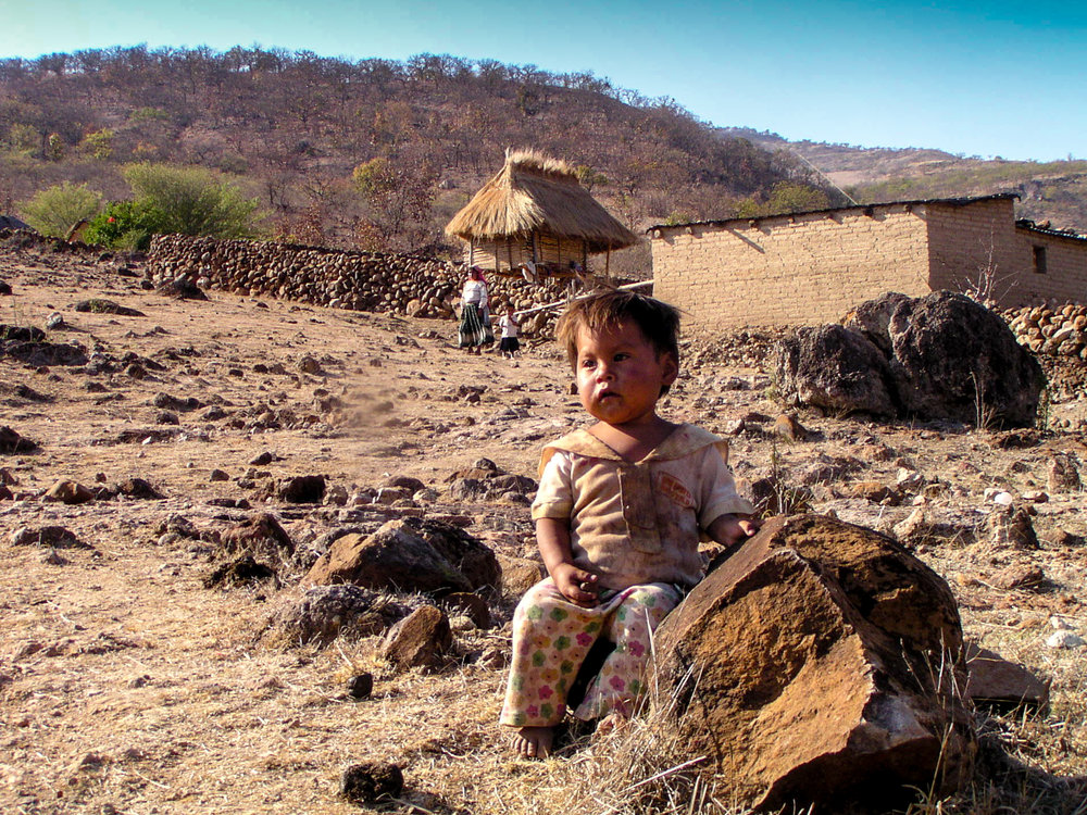 A child sits outside a traditional Wixarika house