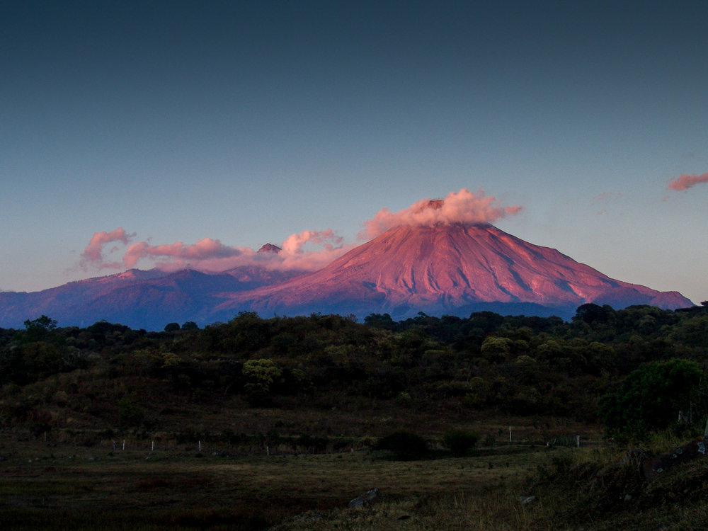 The last rays of the sun hit the  Volcan and Nevado de Colima