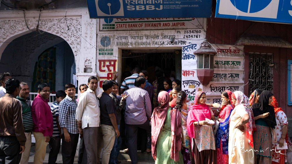 Males and females line up in separate queues outside of a bank in the Old City (Jodhpur)