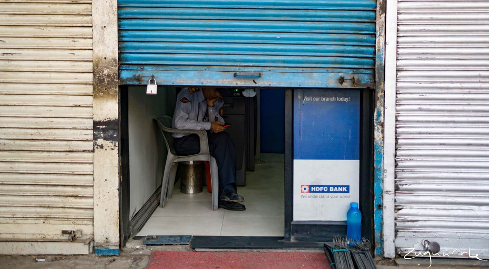 A guard watching over an ATM to inform people when it would be operational again (Delhi)