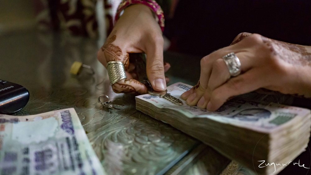 Removing the staple from our stacks of 100 rupee notes (Udaipur)