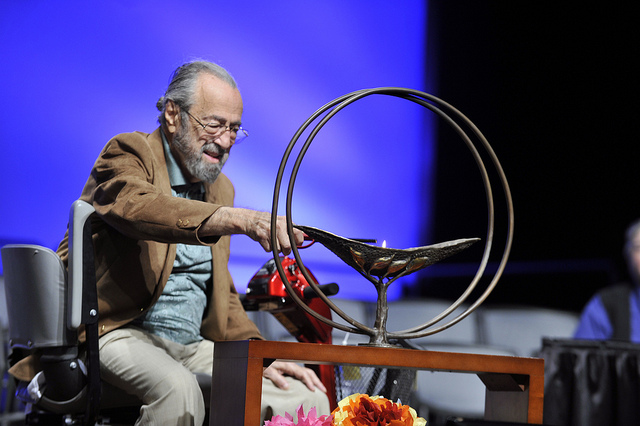 Mordecai Roth, who made the chalice the UUA has used for General Assemblies since 2005, lights the chalice at Friday's plenary. (©Nancy Pierce)