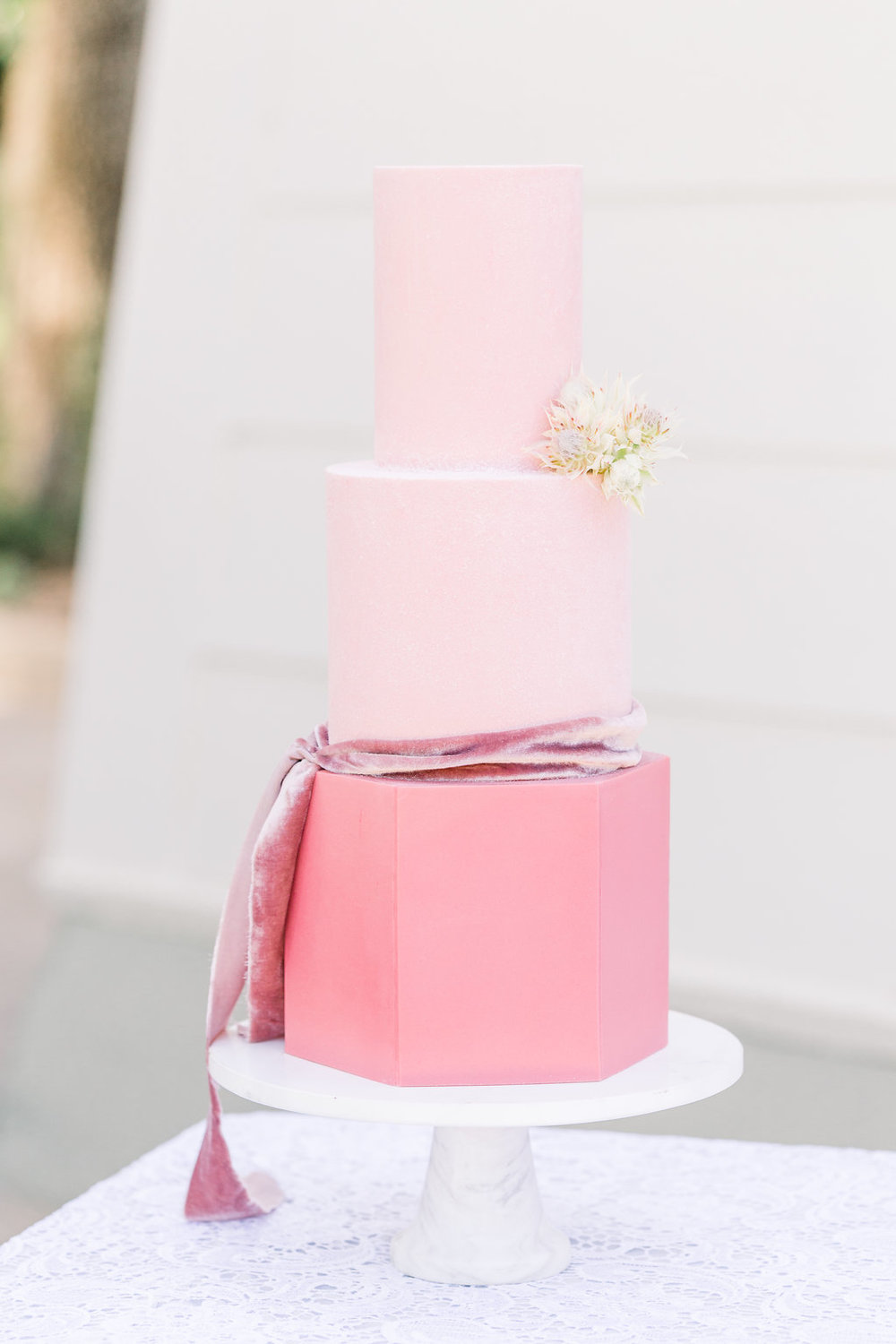 Pink wedding cake on white cake stand and white lace table linen