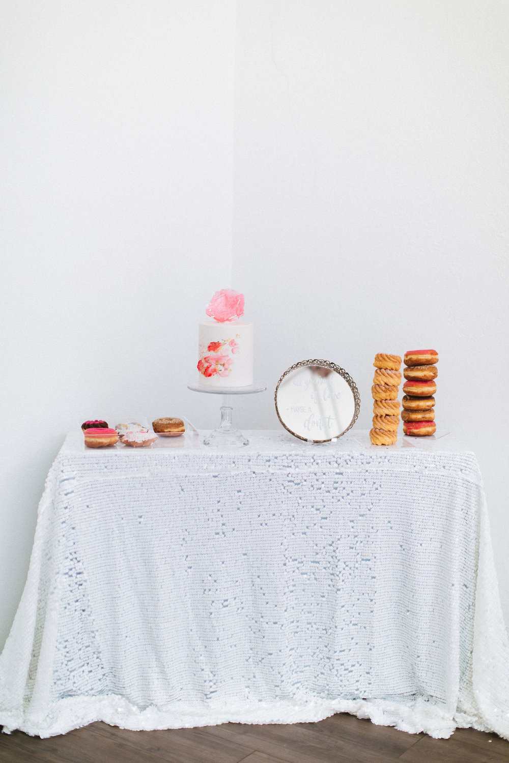 pretty cake and dessert table for galentines featuring white sequined table cloth and transparent cake stand