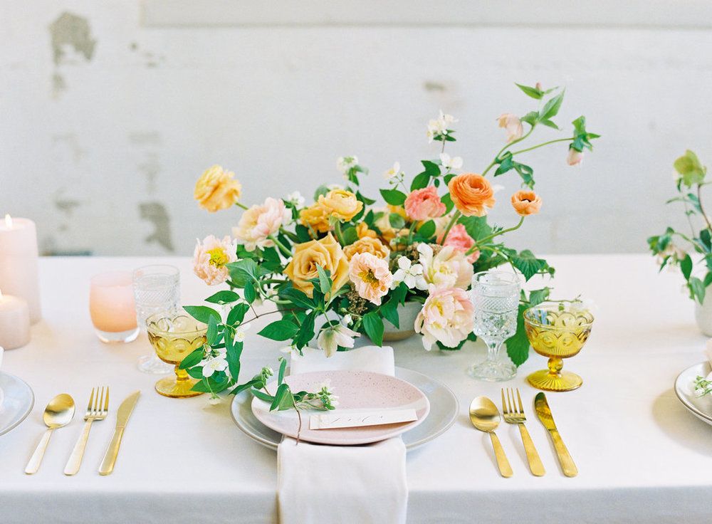 Spring floral arrangement on white linens and gold tableware