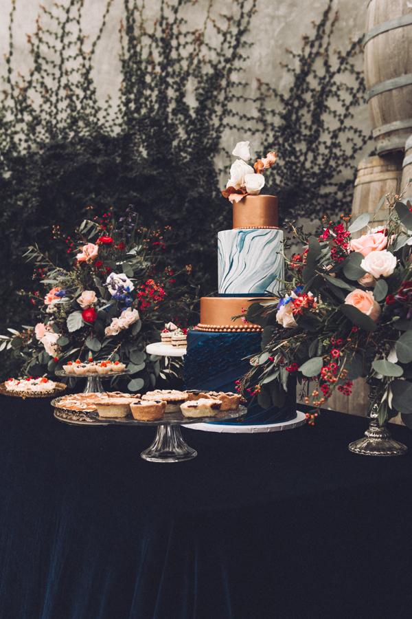 Wedding cake and dessert masterpiece on gorgeous dark blue silk velvet table linen