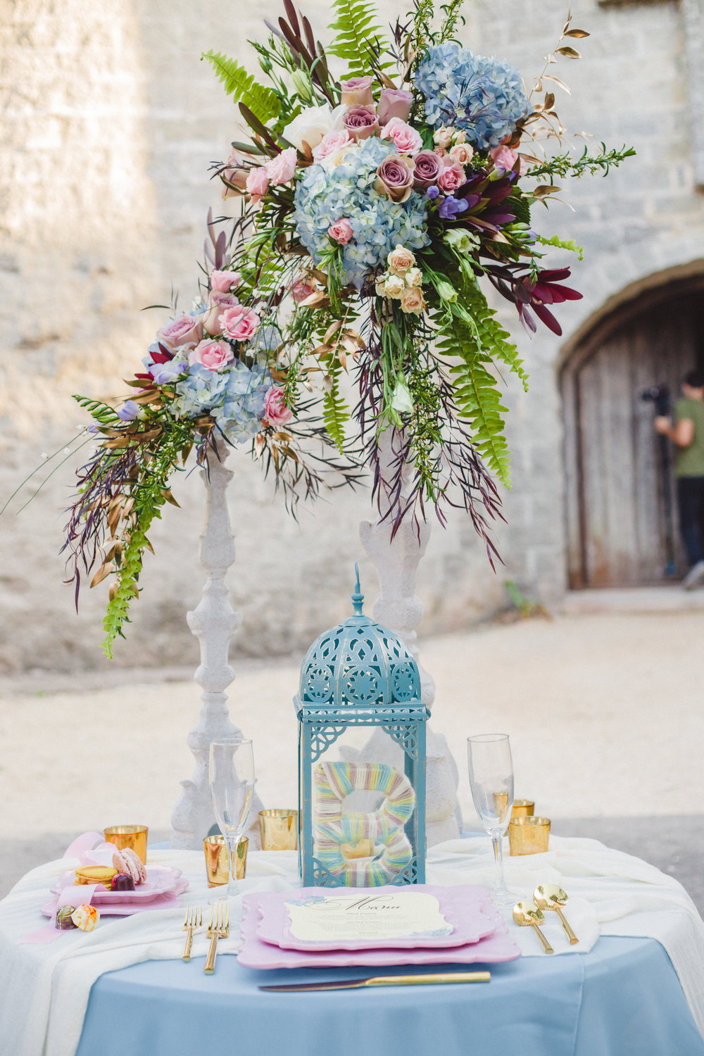 gold and pastel castle wedding tablescape using blue silk table linens and white silk chiffon table runners
