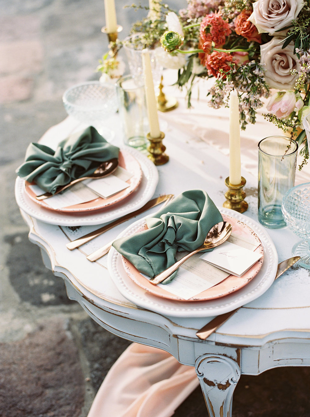 Gorgeous french chateau inspired wedding tablescape with pastel table napkins, rose gold tableware, and flowy peach silk chiffon table runner