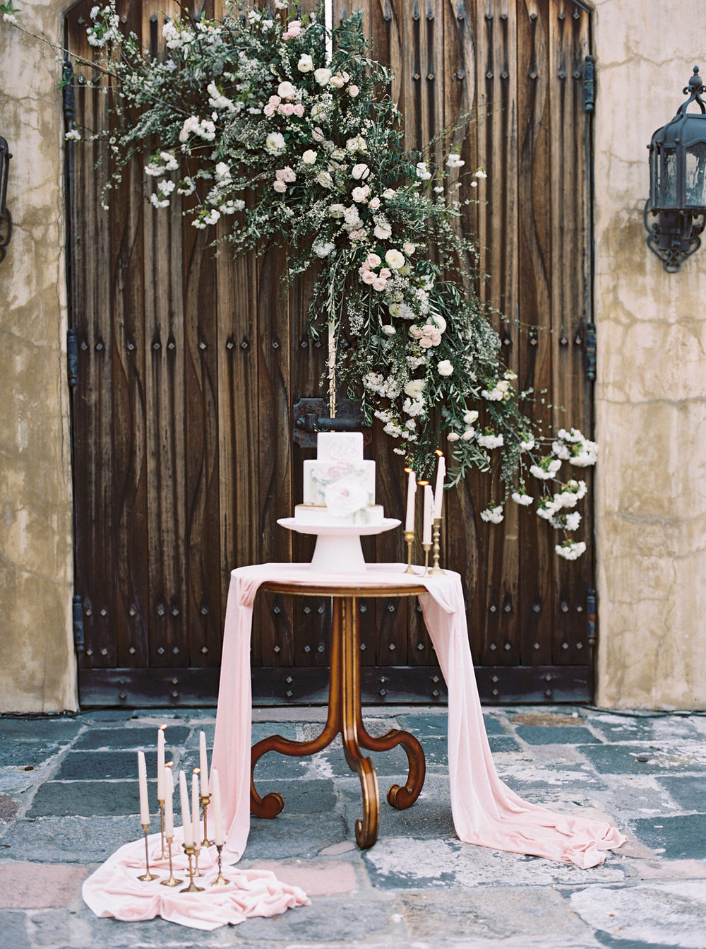 Gorgeous simple oink wedding cake table with long and flowy silk velvet runners