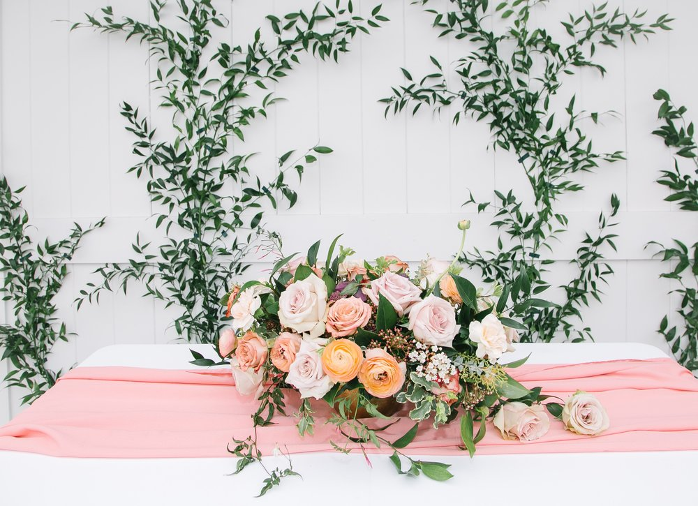 Roses and greens floral arrangement on silk chiffon table runner for Easter and events tablescape