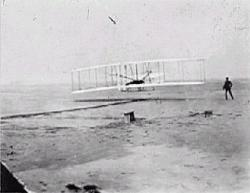 First flight - Orville Wright leaves the ground in the first manned, fully steerable, propelled aircraft Dec. 17, 1903. He is watched by his brother Wilbur and their friend, John Daniels, who took the photograph. Image courtesy of the Wright Brothers Aeroplane Company and Museum of Pioneer Aviation.