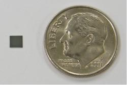 Figure 6: The final prosthetic retina device was 2.5 mm2 in size and consisted of roughly 1900 solar cells giving a resolution of 503 dots/inch. The device is next to a dime to provide a size comparison.