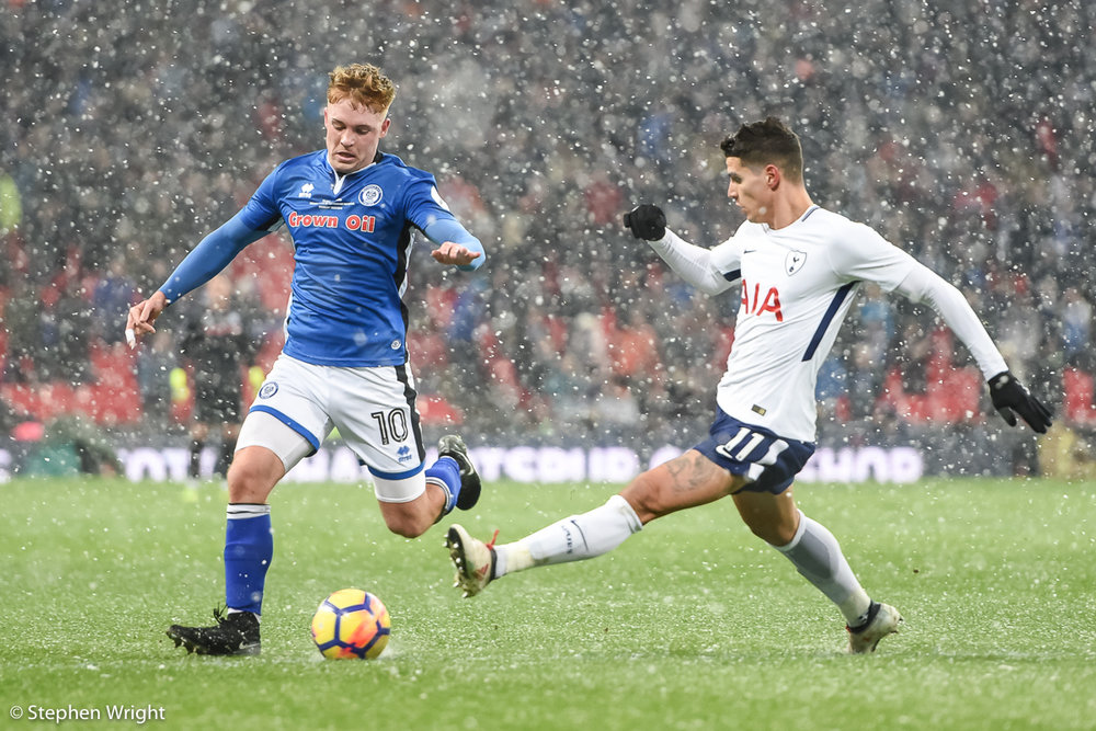 Callum Camps  of  Rochdale  and  Erik Lamela  of  Tottenham Hotspur  battle for the ball.