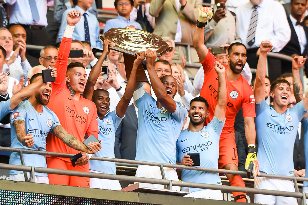 Vincent Kompany  lifts the  Community Shield  after beating  Chelsea  at  Wembley .
