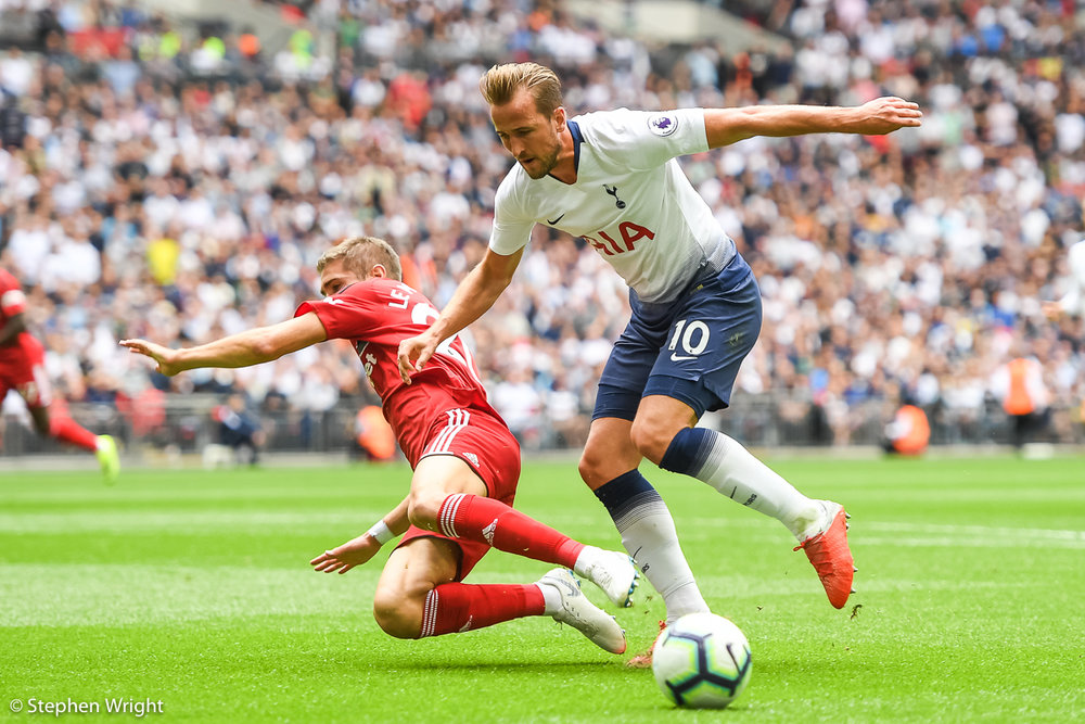 Harry Kane of  Tottenham Hotspur  charges past  Fulham   Maxime Le Marchand  during the  Premier League  at  Wembley Stadium .