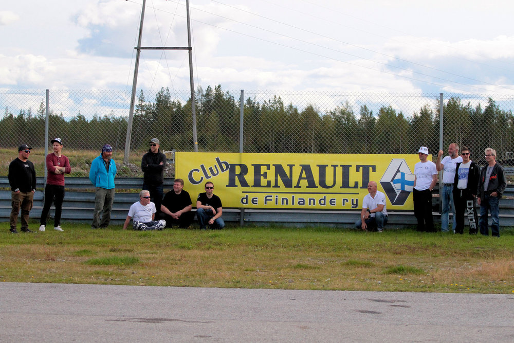 Osa poppoosta poseeraamassa tapahtuman toisen sponsorin eli Club Renault De Finlande plakaatin kanssa.