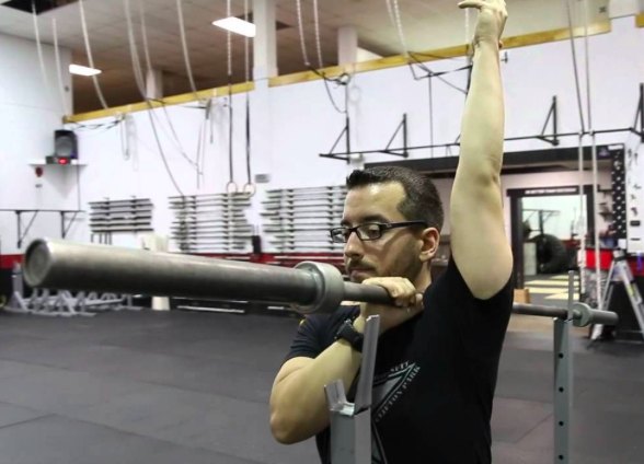 Pin your upper trap with a barbell. While holding the bar down, move the straight arm through full range of motion. Try to keep the elbow locked out, palm faced in, and bicep as close to ear as possible at the top. Continue to move arm up and down for 2 min per side.