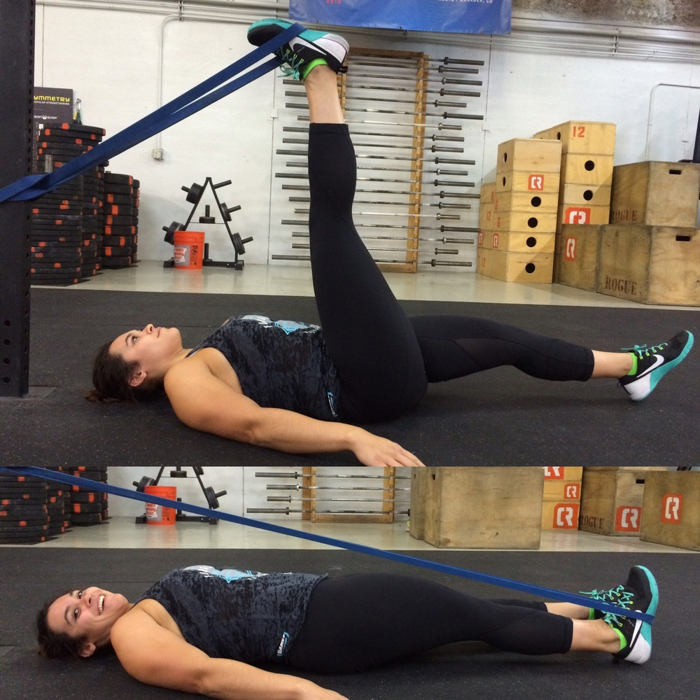 Finally, you get to lay down!! Please do not be fooled by my beautiful model's sweet smile, this stretch is a doozy on the hammy. Keep the monster band attached to the rig at about hip height. Lay down on your back with your head pointed towards the rig and your feet away from it. Wrap the band around the sole of your foot, close to your heel so it doesn't slip off. You can brace yourself with your arms along your side or hold onto the rig behind your head. Keep your left leg straight with your toe pointed up. In the most humanely possible controlled way, lower your right heel to touch the floor briefly before raising the leg back up. DO NOT let your leg boomerang back towards the rig. Try counting to three or four Mississippis on the way up and the way back down. Complete 20 reps per leg. And yes, the pleasurable burning sensation on the back of your leg is totally normal and good for you.