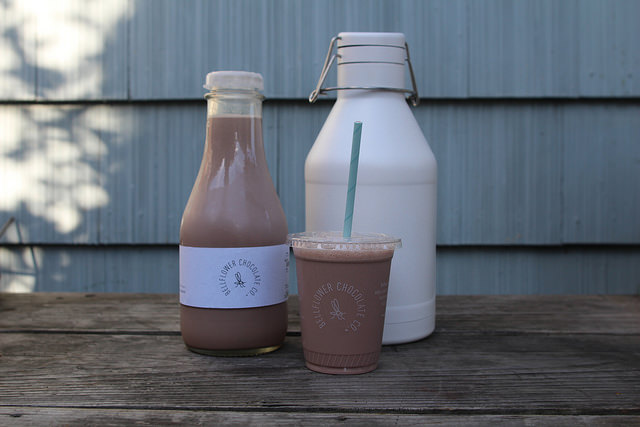 Cups and growlers of Bellflower Chocolate Company's botanical, bean-to-bottle™ chocolate milk.