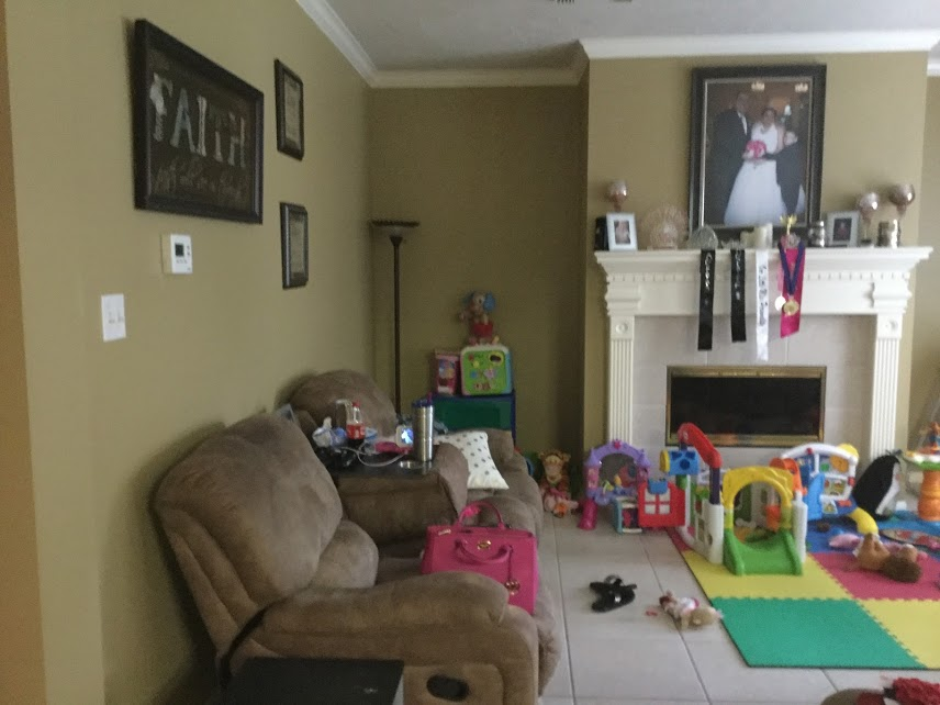 Before... - This young family didn't know how to arrange their home around all the baby's play things.